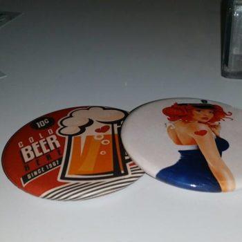 Objet Publicitaire mirroir avec un chope de bière avec un coeur aux couleur rouge, noir et blanc ainsi qu'un pins blanc avec une femme au cheveux orange, une robe bleu et blanche avec une casquette martime et un coeur rouge sur le bras