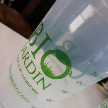 Objet Publicitaire Verre en plastique transparent, avec une écrite verte Bio jardin, site internet : www.biojardin.com avec les graduations sur les côtés. Le O de Bio est représenté avec une feuille et de la pelouse à l'intérieur du O