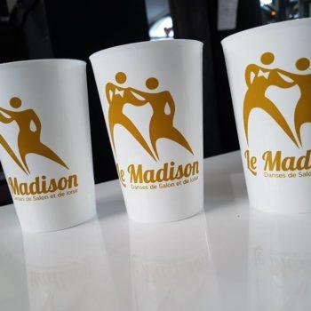 3 verres en plastique blanc, avec sur chaque gobelets un homme et une femme en jaune orangé avec écrit le mot Madison
