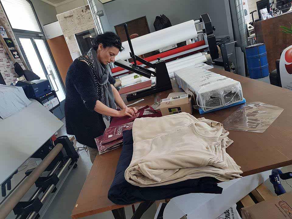 Impression publicitaire, une femme s'occupe des impressions textiles, dans une entreprise de publicité avec des vêtements autour