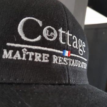 Impression textile sur casquette noir avec inscrit cottage maître restaurant en blanc avec le drapeau de la france