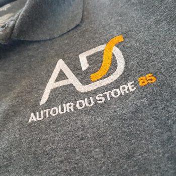 Impression textile sur polo gris avec inscrit AD autour du store 85 en blanc et orange