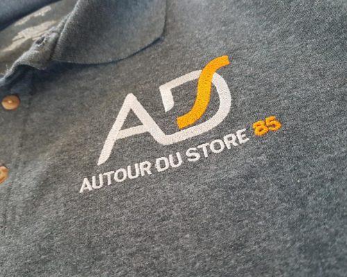 Impression textile sur polo gris inscrit en blanc et orange AD autour du store 85