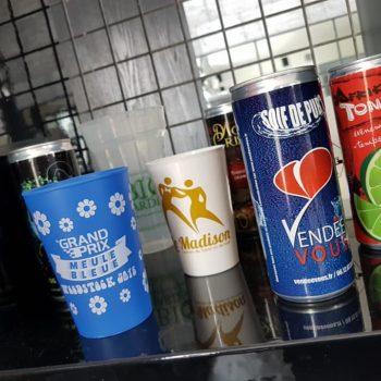 4 canettes de boissons énergisantes et 3 gobelets en plastique personnalisés et situés dans une cuisine