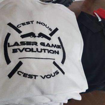 Impression textile sur polo blanc avec inscrit en noir dans un cercle c'est nous LASER GAME EVOLUTION c'est vous