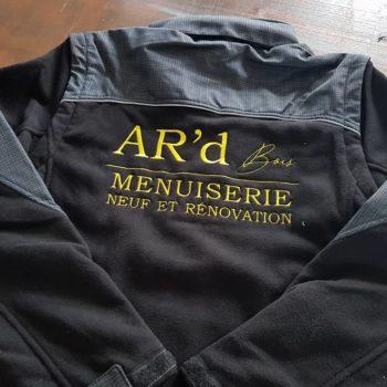 Impression textile sur un manteau noir et gris avec inscrit en jaune AR'd Bois, menuiserie neuf et rénovation