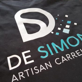 Impression textile sur tee shirt noir, inscrit en blanc et bleu DE SIMON ARTISAN CARRELEUR