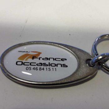 Objet Publicitaire Porte clé oval en métal avec un fond blanc et inscrit réseau France Occasions, 05 46 84 15 11