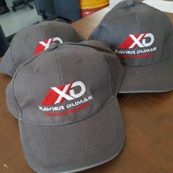 Impression textile trois casquettes gris avec inscrit XD xavier dumas menuiserie en blanc et rouge
