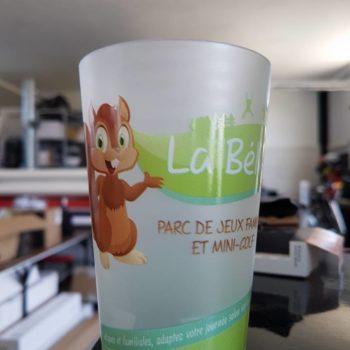 Objet Publicitaire Gobelet en plastique blanc avec un écureuil à gauche, y est inscrit le nom du parc La Bélière, parc de jeux famille et mini golf à Talmont Saint Hilaire