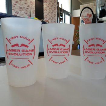 Objet Publicitaire 3 gobolets en plastique blanc avec inscrit en rouge : C'est nous, LASER GAME EVOLUTION, c'est vous dans un cercle rouge avec deux pistolets