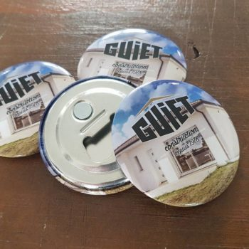 4 pins dont 1 retourné avec inscrit le nom de la marque GUIET construction depuis 1978 avec un fonc avec une maison de la pelouse et le ciel bleu au dessus