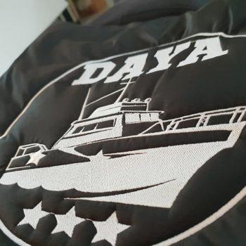 Impression textile, logo day avec une bateau et trois étoiles en blanc sur une doudoune noir