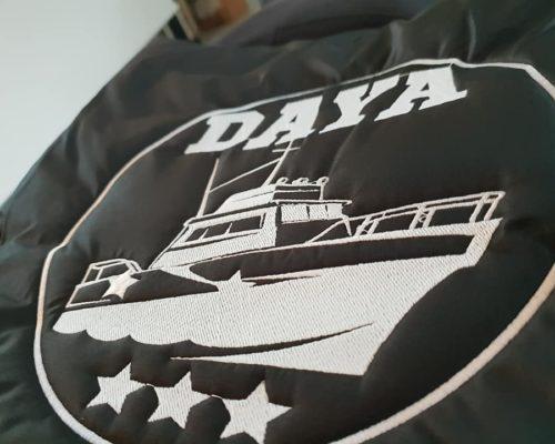 Impression textile sur doudoune noir avec inscrit dans un cercle blanc daya avec un batezu et trois étoiles en blanc