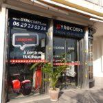 Enseigne et façade aux couleurs blanc, noir et rouge pour des locations et vente de vélos et trotinettes