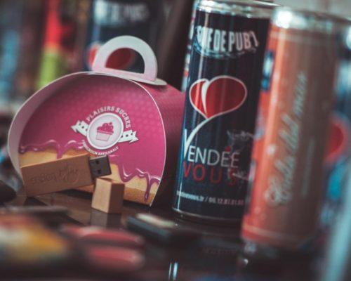 Objet publicitaire avec deux canettes de boisssons énergisantes avec le logo coeur de Vendée Vous ainsi qu'une boîte et une clée USB personnalisés